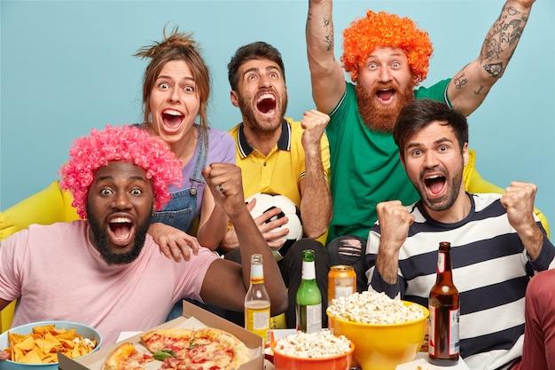 Wypoczynek, sport, pojęcie szczęścia. ponad emocjonalni szczęśliwi przyjaciele podnoszą ręce, głośno krzyczą, celebrują gola, cieszą się ze zwycięstwa popularnej drużyny piłkarskiej, jedzą przekąski, piją alkohol, pozują w pomieszczeniach