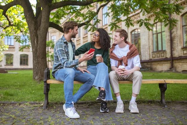 Wypoczynek. trzech przyjaciół spędzających czas w parku i rozmawiających