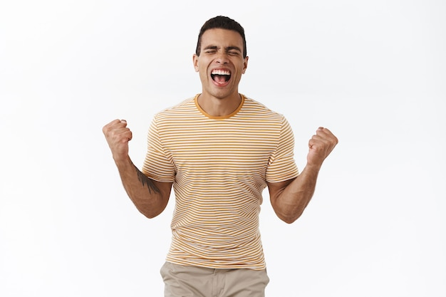 Wypompowany szczęśliwy facet osiąga sukces, świętuje, krzyczy ze szczęścia z zamkniętymi oczami i zaciśniętymi pięściami