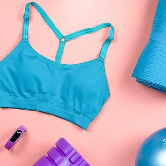 Wyposażenie fitness. rozmieść akcesoria i ubrania do ćwiczeń dla kobiet. widok z góry, tło fitness