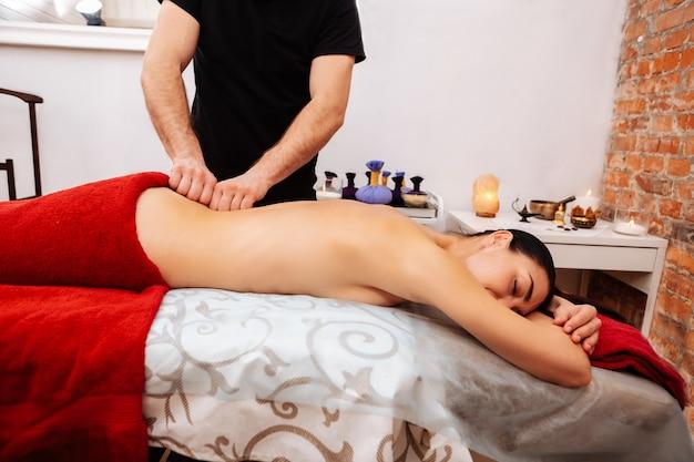 Wyposażona szafka. mocno wysportowany masażysta w czarnym mundurze, miażdżący kręcenie leżącej kobiety, podczas gdy ona spokojnie leży