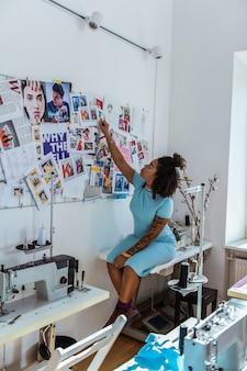Wyposażone studio. krótkowłosa dama z niechlujną bułeczką siedząca na stole i sprawdzająca swoją ścianę inspiracji