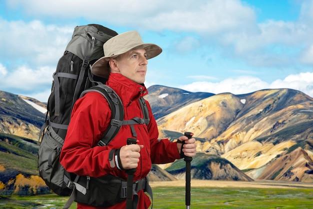 Wyposażony w podróżnika w czerwonej kurtce z kijkami trekkingowymi spogląda w dal. piękny i kolorowy krajobraz górski w landmannalaugar na islandii