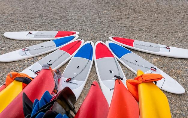 Wypożyczalnia desek sup i kajaków na plaży. deski surfingowe, wiele różnych desek surfingowych na plaży, sporty wodne, szczęśliwe, aktywne wakacje. rząd desek do wiosłowania stand up gotowy do wypożyczenia.