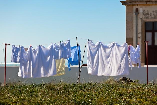 Wyprane ubrania wiszące na zewnątrz starego budynku, wybrzeże portugalii
