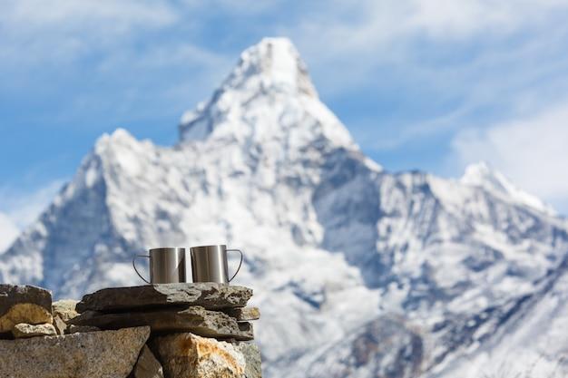 Wyprawa do everest base camp. dwie filiżanki herbaty na tle góry ama dablam w centrum uwagi. tło góry niewyraźne.
