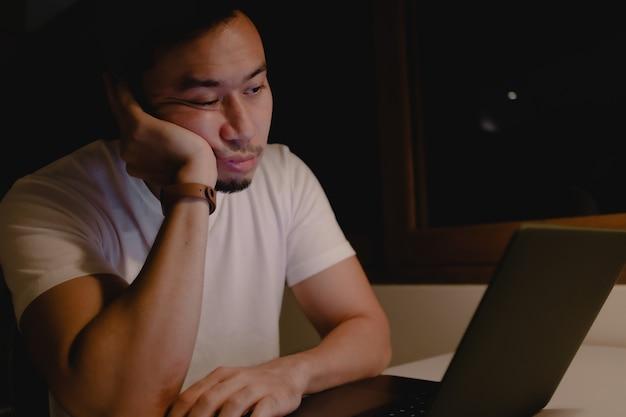 Wypróbowany i zaspany mężczyzna pracuje późno w nocy ze swoim laptopem