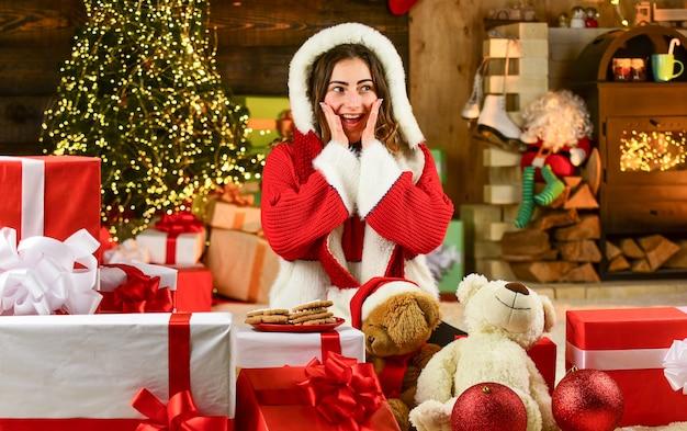 Wyprzedaż ferii zimowych. domowa impreza z bożonarodzeniowymi ciasteczkami. szczęśliwa dziewczyna zrobiła ciasteczka dla świętego mikołaja. santa kobieta czuje szczęście w nowym roku. dziewczyna santa wśród świątecznych prezentów i prezentów. zakupy w czarny piątek.