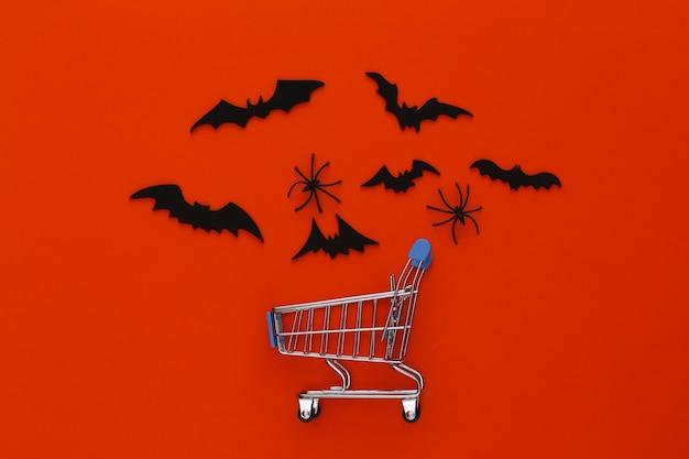 Wyprzedaż na halloween, zakupy. wózek w supermarkecie i latające nietoperze, pająki na pomarańczowo. halloweenowa dekoracja