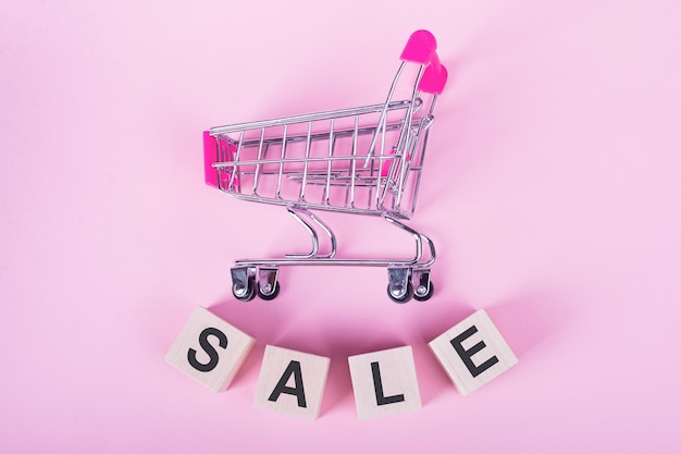 Wyprzedaż - słowo na drewnianych kostkach, na różowym tle z wózkiem na zakupy.