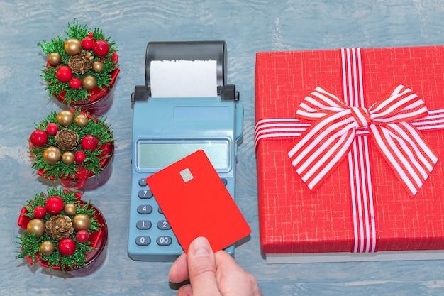 Wyprzedaż świąteczna. dłoń trzymająca czerwoną kartę bankową nad kasą w pobliżu czerwonego pudełka ze wstążką i małych choinek z szyszkami. zakupy online. kupowanie prezentów na nowy rok i boże narodzenie