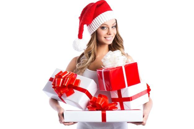 Wyprzedaż świąteczna i noworoczna. dziewczyna w santa hat z prezentami na białym tle.