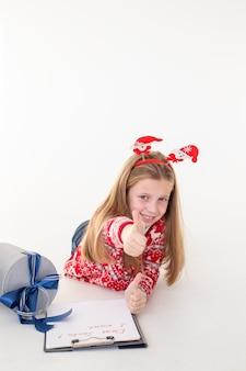 Wyprzedaż świąteczna. słodkie dziecko trzymając pióro i pisać na białej powierzchni. nowy rok sprzedaż