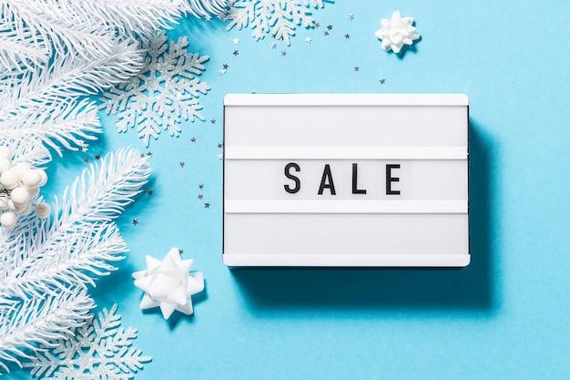 Wyprzedaż tekstowa na lightbox na jasnoniebieskim tle z białymi dekoracjami świątecznymi
