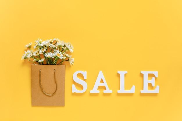 Wyprzedaż tekstu z białych liter i kwiatów rumianku polnego w torbie na zakupy na żółtym tle