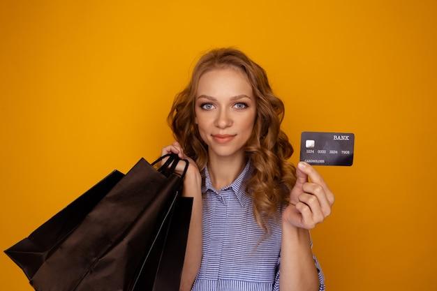 Wyprzedaż zakupów. ładna kobieta z torby i karty kredytowej w żółtym studiu.