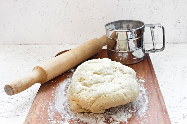Wyrabia ciasto. ciasto do gotowania. ciasto na drewnianej desce z wałkiem do ciasta.