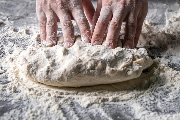 Wyrabianie ciasta kobiecymi rękami w piekarni, produkcja wyrobów mącznych