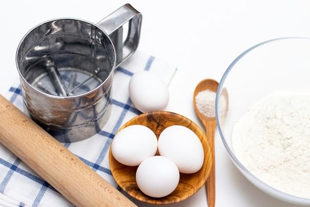 Wyrabianie ciasta na chleb lub domowe wypieki. składniki na stole: jajka, mąka, sól, wałek do ciasta