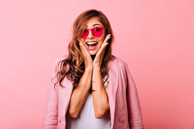 Wyrafinowana biała dama pozuje z zaskoczonym uśmiechem na różowo. cudowna długowłosa dziewczyna w śmiesznych różowych okularach wygłupia się.