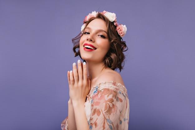 Wyrafinowana biała modelka w romantycznym stroju ze śmiechem. debonair krótkowłosa dziewczyna z kwiatami na głowie uśmiechnięta.