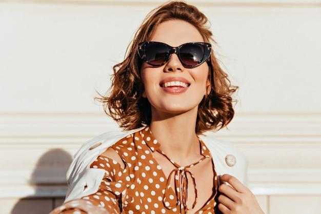 Wyrafinowana dziewczyna co selfie z uśmiechem. ładna brązowowłosa kobieta w okularach z uśmiechem