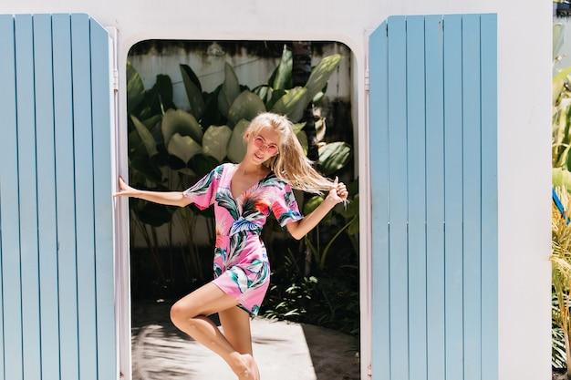Wyrafinowana dziewczyna stojąca na jednej nodze i wyrażająca radość.