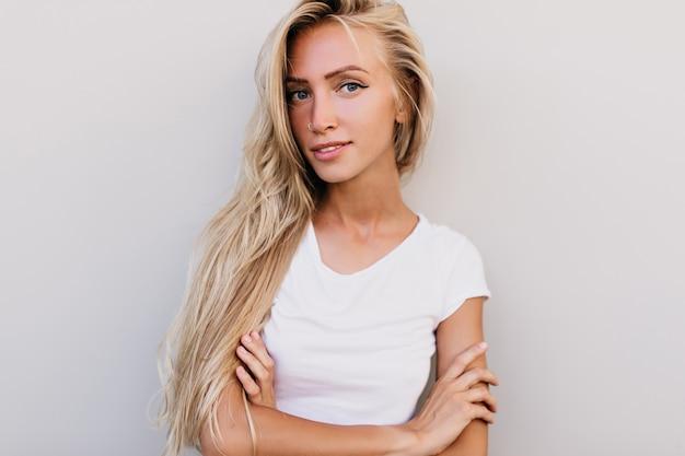Wyrafinowana europejska kobieta z założonymi rękami. entuzjastyczna młoda dama o blond włosach podczas sesji zdjęciowej.