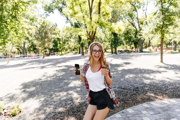 Wyrafinowana jasnowłosa dama w czarnych szortach śmiejąca się w parku. wspaniała europejska dziewczyna z filiżanką kawy wygłupiać się w letni weekend.