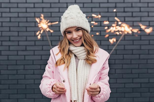 Wyrafinowana kaukaska dziewczyna spędzająca ferie zimowe w dobrym humorze. zewnątrz portret marzycielskiej młodej kobiety z zimnymi ogniami, zabawy.