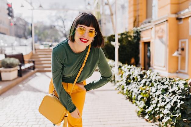 Wyrafinowana kobieta z jasnym makijażem pozuje na ulicy w żółtych okularach przeciwsłonecznych. odkryty strzał uroczej dziewczyny kaukaski z czarnymi włosami, śmiejąc się w dobry wiosenny poranek.