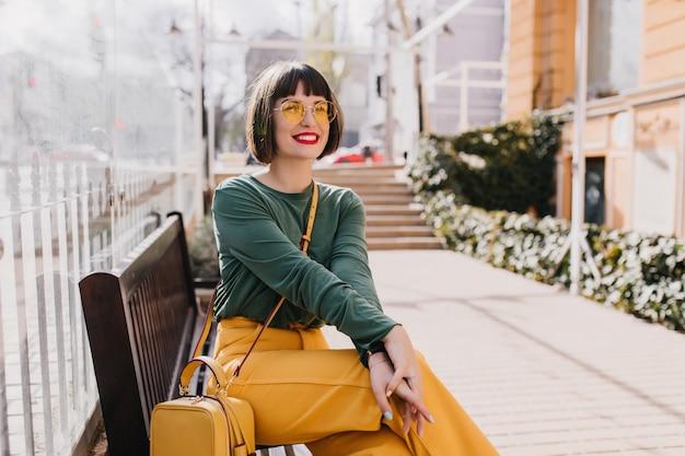 Wyrafinowana młoda kobieta z krótkimi włosami siedzi na ławce i uśmiecha się. zewnętrzne zdjęcie niesamowitej dziewczyny kaukaskiej cieszącej się dobrym wiosennym dniem.