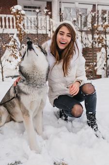 Wyrafinowana modelka w ciepłych ubraniach wygłupia się z psem husky podczas ferii zimowych. plenerowy portret pięknej młodej damy bawi się ze zwierzakiem w grudniowy poranek.