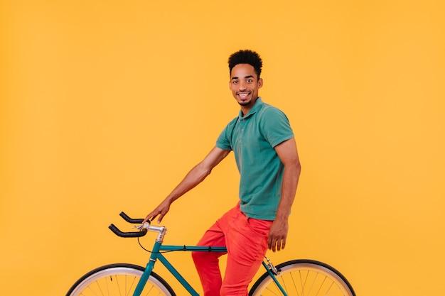 Wyrafinowany mężczyzna rowerzysta pozuje z uśmiechem. zainteresowany brunetka facet siedzi na rowerze w pobliżu żółtej ściany.