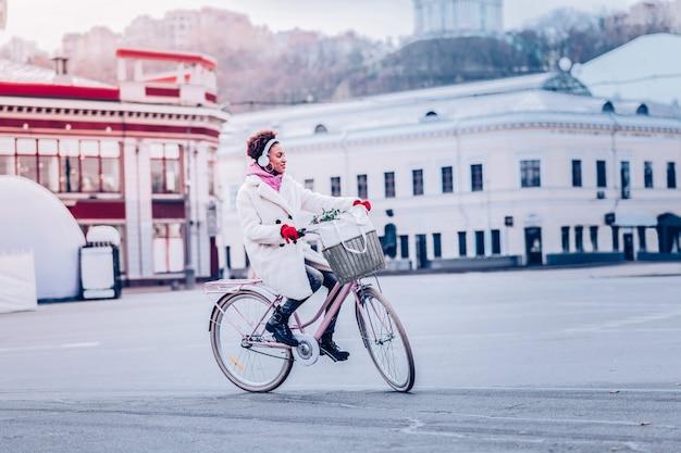 Wyraź pozytywne nastawienie. miła międzynarodowa dziewczyna ubrana w ekologiczne futro i siedząca na rowerze