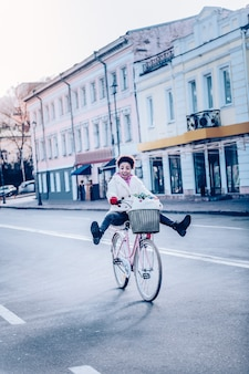 Wyraź pozytywne nastawienie. niesamowita dziewczyna czująca szczęście podczas szybkiej jazdy na rowerze