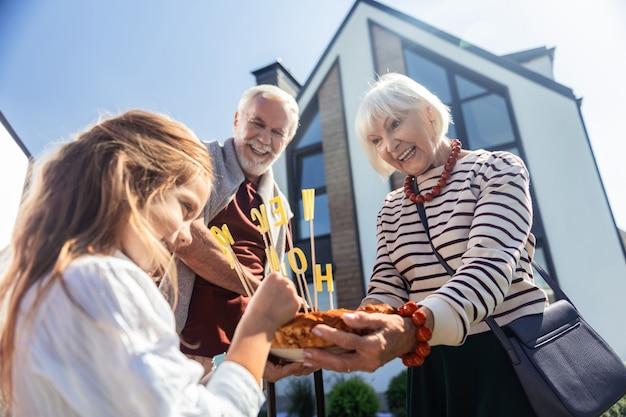 Wyraź pozytywne nastawienie. szczęśliwa dojrzała kobieta trzyma tort, patrząc na jej wnuka