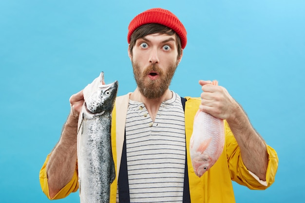 Wyraz twarzy, emocje i uczucia człowieka. zabawny, zdumiony młody rybak w czerwonym kapeluszu i żółtym płaszczu przeciwdeszczowym, pozujący przy ścianie z dwiema rybami, zdziwiony świetnym połowem