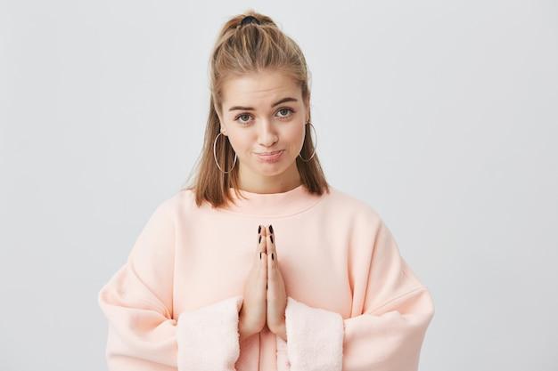 Wyraz twarzy, emocje, mowa ciała. dobrze wyglądająca urocza dziewczyna ubrana na różowo trzymająca przed sobą zaciśnięte dłonie, o wyrazie żalu i żalu, błagająca o wybaczenie.