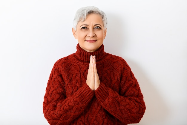 Wyraz twarzy, emocje, uczucia i reakcje człowieka. izolowane obraz pozytywnej wesołej kobiety na emeryturze z krótkimi włosami, patrząc z radosnym uśmiechem, trzymając się za ręce w modlitwie, mając pełen nadziei wygląd