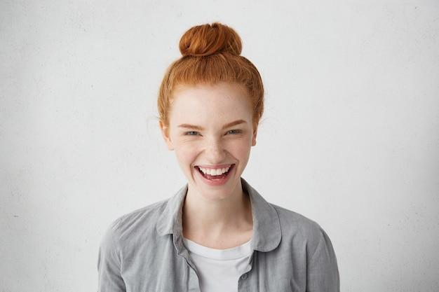 Wyraz twarzy, emocje, uczucia, reakcje i postawa człowieka. wesoła ruda europejska dziewczyna z piegami śmiejąca się radośnie