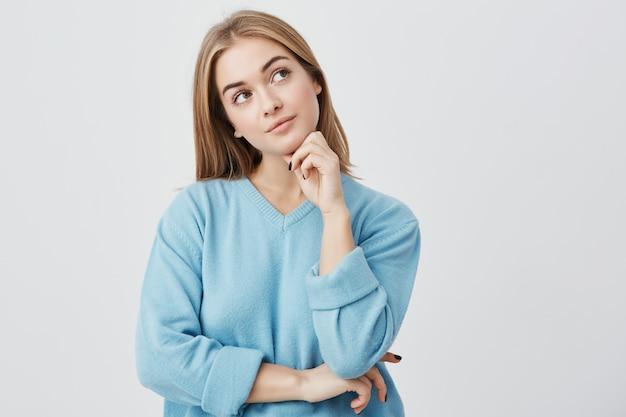 Wyraz twarzy i emocje. przemyślana młoda ładna dziewczyna w niebieskim swetrze trzymająca rękę pod głową, o wątpliwym spojrzeniu, a jednocześnie nie może zdecydować, jakie ubrania założyć na przyjęcie urodzinowe przyjaciela