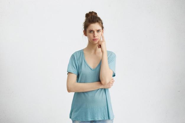 Wyraz twarzy i emocje. rozważna młoda kobieta w ubranie, trzymając palec na głowie
