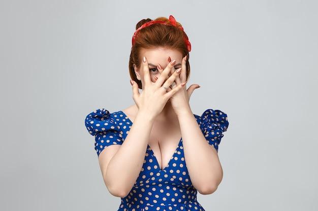Wyraz twarzy, uczucia i język ciała człowieka. studio strzał przerażonej młodej damy ubranej w stylowe ubrania vintage zakrywające twarz obiema rękami, podglądanie kamery przez palce