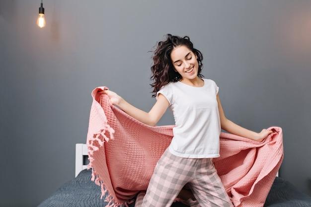 Wyrażająca prawdziwe pozytywne emocje młodej podekscytowanej brunetki w piżamie bawiącej się różowym kocem. relaks w domu w nowoczesnym mieszkaniu