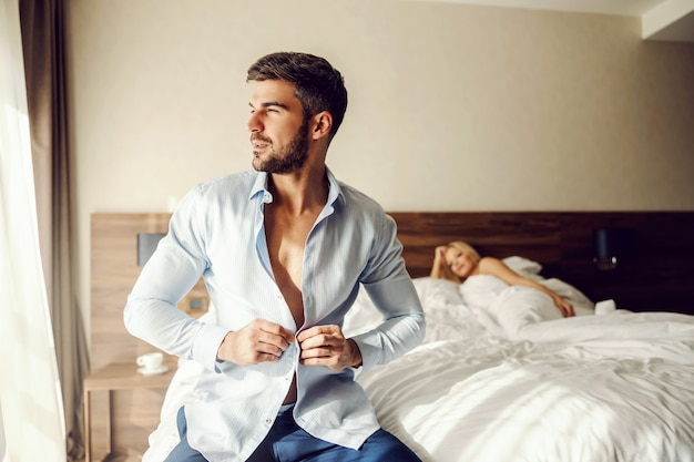 Wyrażanie czułych i pełnych namiętności emocji w pokoju hotelowym. śpiąca królewna leży na łóżku i patrzy na przystojnego, dobrze ubranego mężczyznę szykującego się do wyjścia na spotkanie biznesowe. miłość pasja