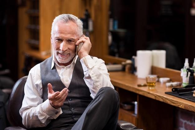 Wyrażanie emocji. przystojny brodaty starszy mężczyzna siedzi na fotelu i aktywnie gestykuluje podczas rozmowy przez telefon komórkowy w zakładzie fryzjerskim.