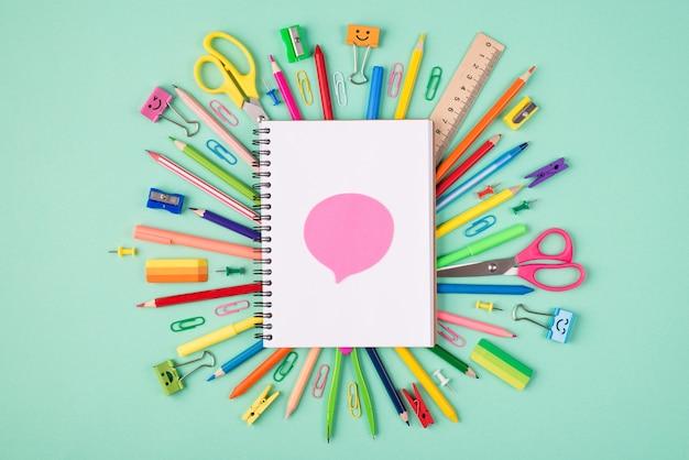 Wyrażanie koncepcji forum opinii. górne nad widokiem z góry zdjęcie kolorowej papeterii i pustego notatnika z różową bańką na górze na białym tle na turkusowym tle