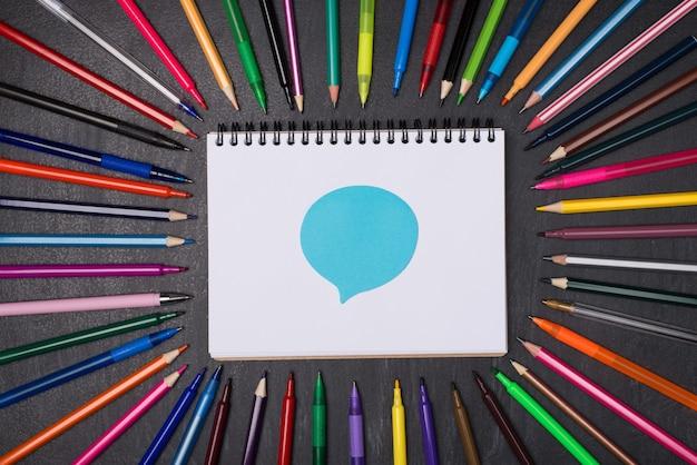 Wyrażanie opinii w koncepcji szkoły. górne nad głową flatlay widok zdjęcie kolorowych długopisów i ołówków wokół pustego notatnika z niebieską naklejką bąbelkową na białym tle na tablicy