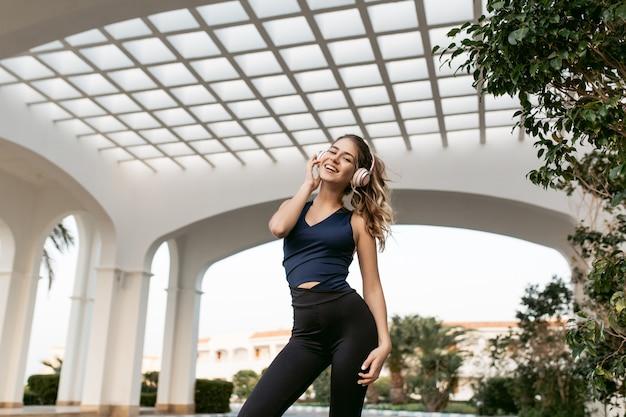 Wyrażanie pozytywnego nastawienia radosnej ładnej kobiety w sportowym stroju poprzez trening uśmiechnięty na wschodniej architekturze. słuchanie muzyki przez słuchawki, szczęście, sportowy styl życia